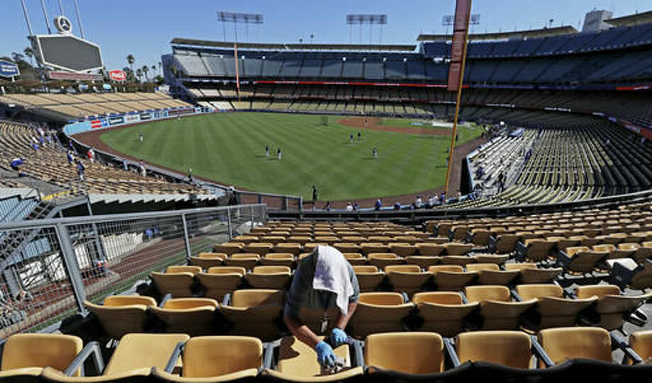 A worker tries to keep cool with a towel over her head as she cleans some seats before Game 5 of the National League baseball championship series between the Chicago Cubs and the Los Angeles Dodgers Thursday, Oct. 20, 2016, in Los Angeles. (AP Photo/Jae C. Hong)
