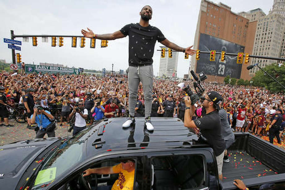 FILE - In this June 22, 2016, file photo, Cleveland Cavaliers' Kyrie Irving stands on the roof of a pickup truck before a parade celebrating the NBA basketball team's championship, in downtown Cleveland. Four months after LeBron James and the Cavaliers ended the city's championship drought at 52 years by winning the NBA title, the Indians are back in the World Series for the first time since 1997. ( (AP Photo/Gene J. Puskar, File)