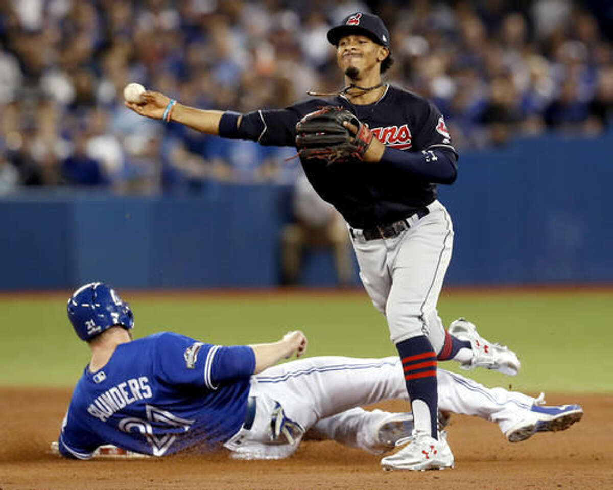 FILE- In this Tuesday Oct. 18, 2016, file photo, Cleveland Indians shortstop Francisco Lindor, right, forces Toronto Blue Jays' Michael Saunders out at second, but, fails to throws Ezequiel Carrera out at first during the second inning in Game 4 of baseball's American League Championship Series in Toronto. A leader in the clubhouse and on the field, Cleveland's 22-years-old exuberant shortstop has blossomed in this postseason will now showcase his immense talents in the World Series. (Mark Blinch/The Canadian Press via AP, File)