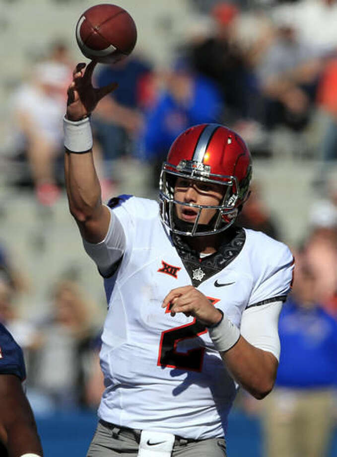 Oklahoma State quarterback Mason Rudolph (2) passes to a teammate during the first half of an NCAA college football game against Kansas in Lawrence, Kan., Saturday, Oct. 22, 2016. (AP Photo/Orlin Wagner)