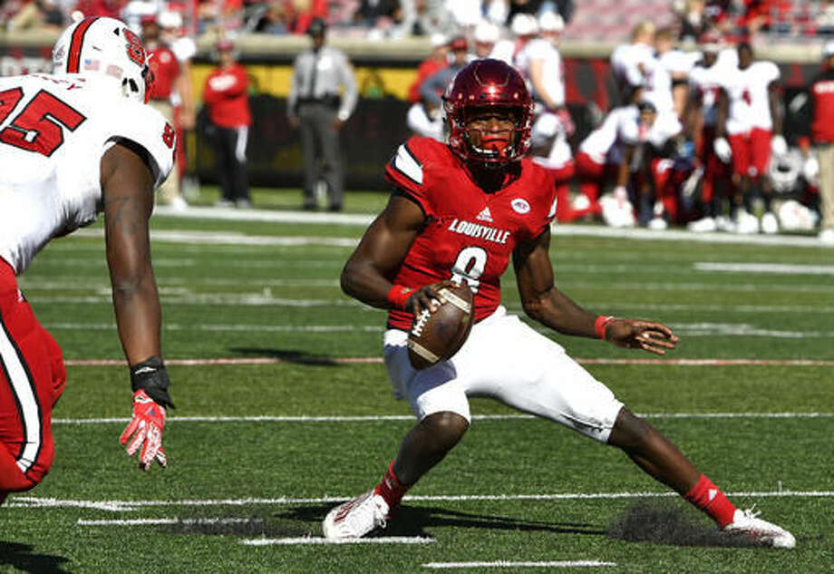 Louisville's Lamar Jackson, (8), attempts to avoid North Carolina State's Tyrone Riley (95) during the second half of their NCAA college football game, Saturday, Oct. 22, 2016, in Louisville, Ky. Louisville won 54-13. (AP Photo/Timothy D. Easley)