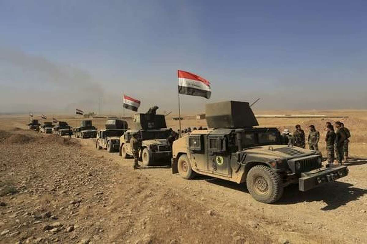 Iraq's elite counterterrorism forces patrol outside the town of Bartella, Iraq, Saturday, Oct. 22, 2016. Iraqi forces retook Bartella, around 15 kilometers (9 miles) east of Mosul, earlier this week, but are still facing pockets of resistance in the area. (AP Photo/Khalid Mohammed)