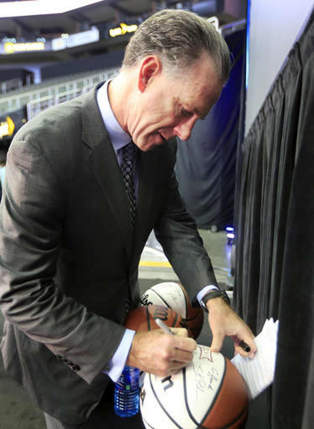 TCU coach Jamie Dixon autographs balls during Big 12 NCAA college basketball media day in Kansas City, Mo., Tuesday, Oct. 25, 2016. (AP Photo/Orlin Wagner)