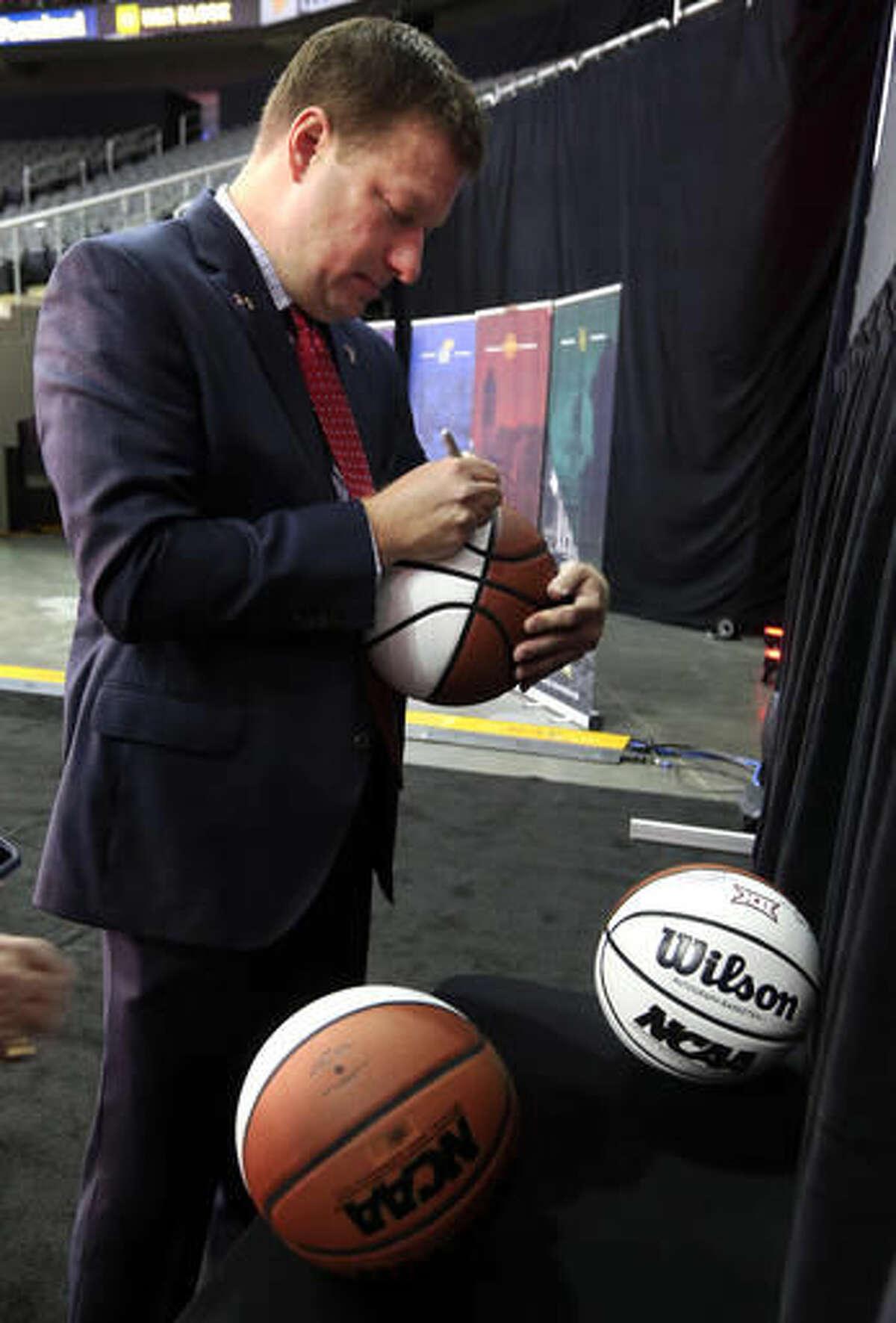 Texas Tech coach Chris Beard autographs basketballs during Big 12 NCAA college basketball media day in Kansas City, Mo., Tuesday, Oct. 25, 2016. (AP Photo/Orlin Wagner)