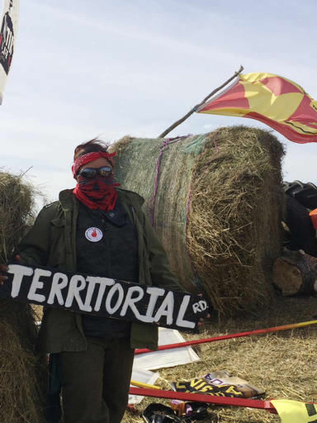 Vanessa Dundon, of White Cone, Ariz., helps handle security Monday, Oct. 24, 2016, at the Dakota Access oil pipeline protest in southern North Dakota. Bagola is sitting atop a pile of logs that protesters prepared to use to block a highway. The long-running dispute over the Dakota Access oil pipeline expanded to private land recently purchased by the pipeline builders, with protesters who say the area rightfully belongs to Native Americans setting up camp and vowing to stay put until the project is stopped. (AP Photo/Blake Nicholson)