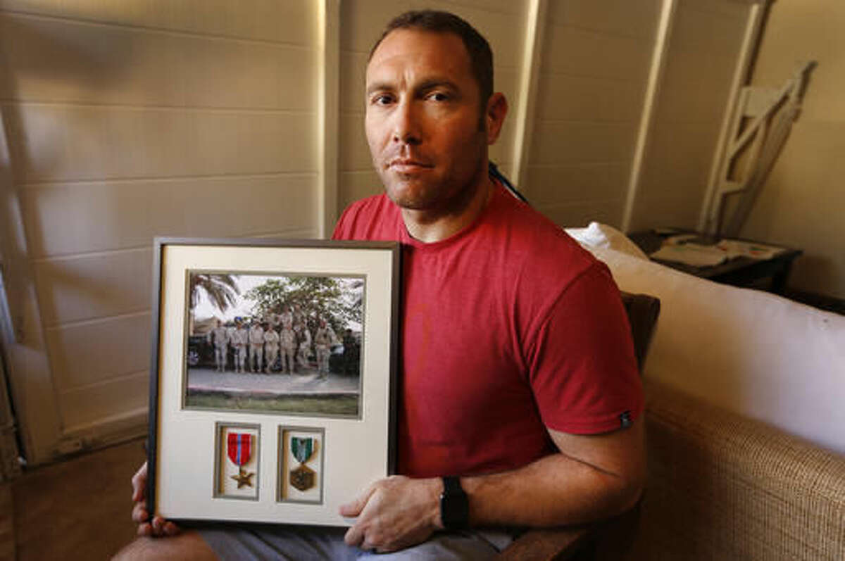 FILE - In this Friday, Oct. 21, 2016 file photo, Robert D'Andrea, a retired Army major and Iraq war veteran, holds a frame with a photo of his team on his first deployment to Iraq in his home in Los Angeles. Nearly 10,000 California National Guard soldiers have been ordered to repay huge enlistment bonuses a decade after signing up to serve in Iraq and Afghanistan, the Los Angeles Times reported Saturday. (Al Seib/Los Angeles Times via AP, File)