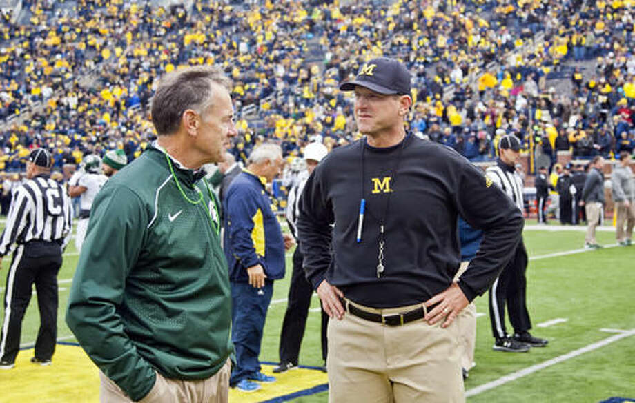 FILE - In this Oct. 17, 2015, file photo, Michigan State head coach Mark Dantonio, left, chats with Michigan head coach Jim Harbaugh before an NCAA college football game in Ann Arbor, Mich. Ohio State's last Saturday to Penn State has created this somewhat uncomfortable situation for their fans to have to pull for their most intense rival. Here's why: The sixth-ranked Buckeyes can win a three-way tiebreaker in the Big Ten East among themselves, Michigan and Penn State if all finish 8-1. But in a head-to-head tiebreaker with the Nittany Lions, Ohio State loses out. (AP Photo/Tony Ding, File)