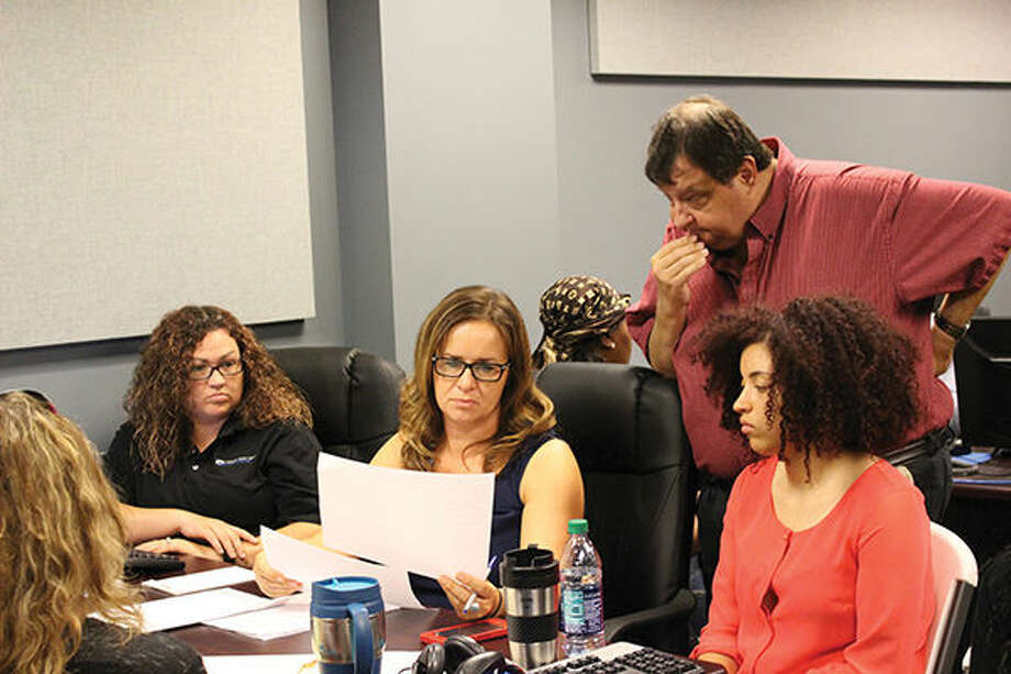 Attorneys and courtroom staff go over an individual's record on Friday, which was Expungement Day in Madison County.