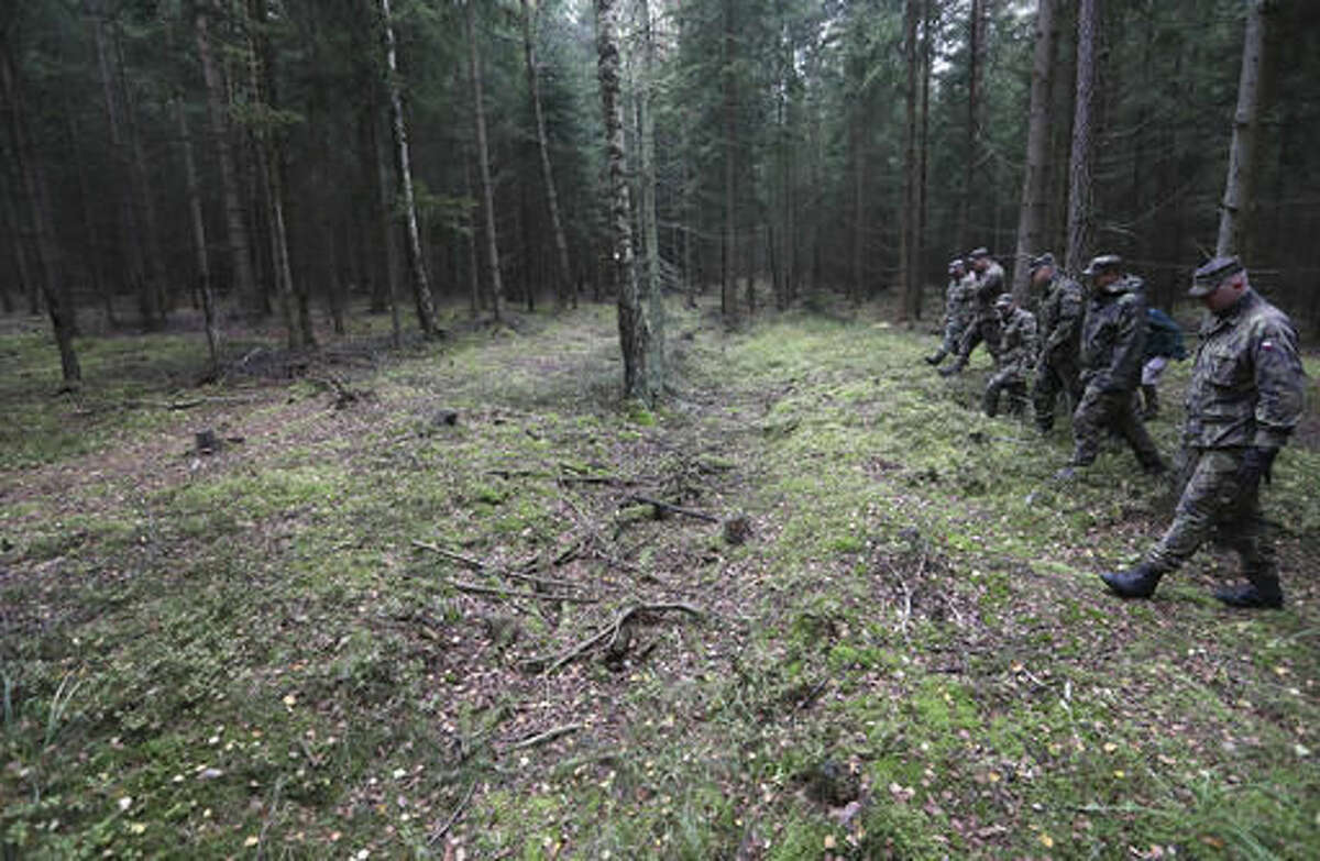 In this picture taken on Tuesday, Oct. 18, 2016, a group of soldiers demonstrates a search for ammunition at the Brdy reserve in Brdy, Czech Republic. A former military zone near Prague which the army used to do artillery training has been turning into a protected nature reserve and opening to the public after almost a century with a big politics decision behind it. (AP Photo/Petr David Josek)