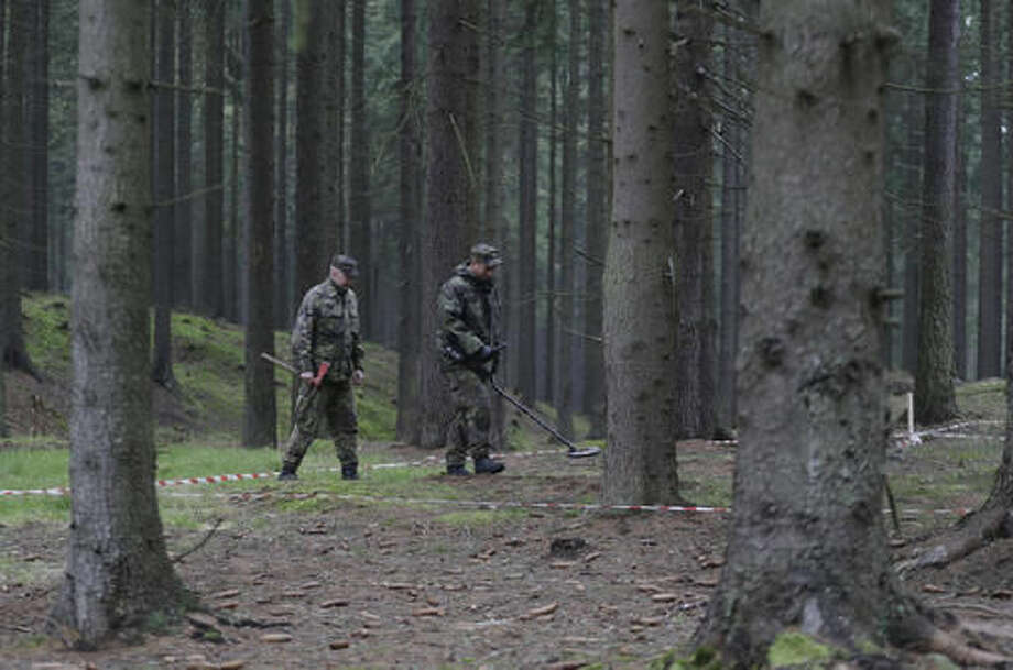 In this picture taken on Tuesday, Oct. 18, 2016, soldiers demonstrate a search for ammunition at the Brdy reserve in Brdy, Czech Republic. A former military zone near Prague which the army used to do artillery training has been turning into a protected nature reserve and opening to the public after almost a century with a big politics decision behind it. (AP Photo/Petr David Josek)