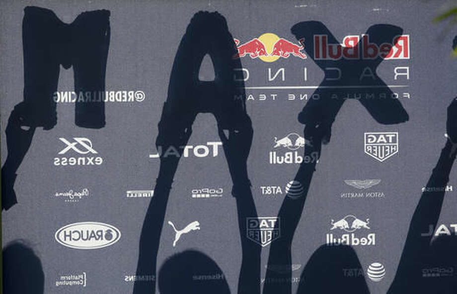 """FILE - In this Sept. 30, 2016, file photo, fans of Red Bull driver Max Verstappen, of the Netherlands, hold up his initials on a sign board in the F1 paddock at the Sepang International Circuit ahead of the first practice session for the Malaysian Formula One Grand Prix in Sepang, Malaysia. """"Mad Max"""" is brash, won't be intimidated and to many, he's a much-needed dose of excitement for Formula One and a future champion. (AP Photo/Joshua Paul, File)"""