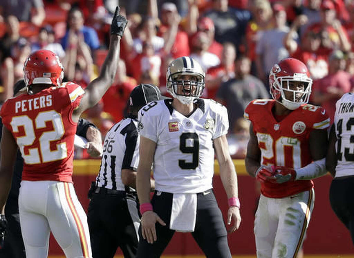 New Orleans Saints quarterback Drew Brees, center, stands between Kansas City Chiefs defensive backs Marcus Peters (22) and Steven Nelson (20) after the final play of an NFL football game Sunday, Oct. 23, 2016, in Kansas City. (AP Photo/Jeff Roberson)