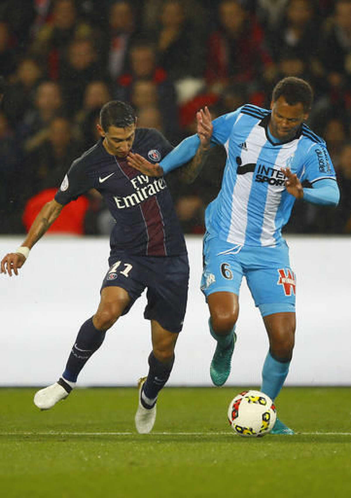 PSG's Angel Di Maria, left, challenges for the ball with Marseille's Rolando Pires Da Fonseca during their French League One soccer match between PSG and Marseille at the Parc des Princes stadium in Paris, France, Sunday, Oct. 23, 2016. (AP Photo/Francois Mori)