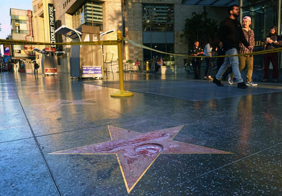 Pedestrians walk past a cordoned off area surrounding the vandalized star for Republican presidential candidate Donald Trump on the Hollywood Walk of Fame, Wednesday, Oct. 26,2016, in Los Angeles. Det. Meghan Aguilar said investigators were called to the scene before dawn Wednesday following reports that Trump's star was destroyed by blows from a hammer. (AP Photo/Richard Vogel)