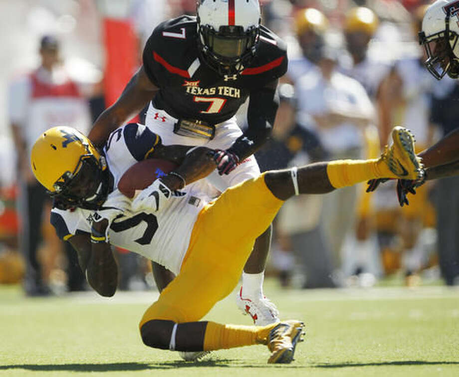 FILE - In this Saturday, Oct. 15, 2016, file photo, West Virginia wide receiver Jovon Durante is tackled by Texas Tech defensive back Jah'shawn Johnson in the second quarter of an NCAA college football game at Jones AT&T Stadium in Lubbock, Texas. Durante was among a group of receivers that made diving catches last week against TCU and will be looking for more on Saturday when No. 10 West Virginia travels to play Oklahoma State. (Mark Rogers/Lubbock Avalanche-Journal via AP, File) /Lubbock Avalanche-Journal via AP)