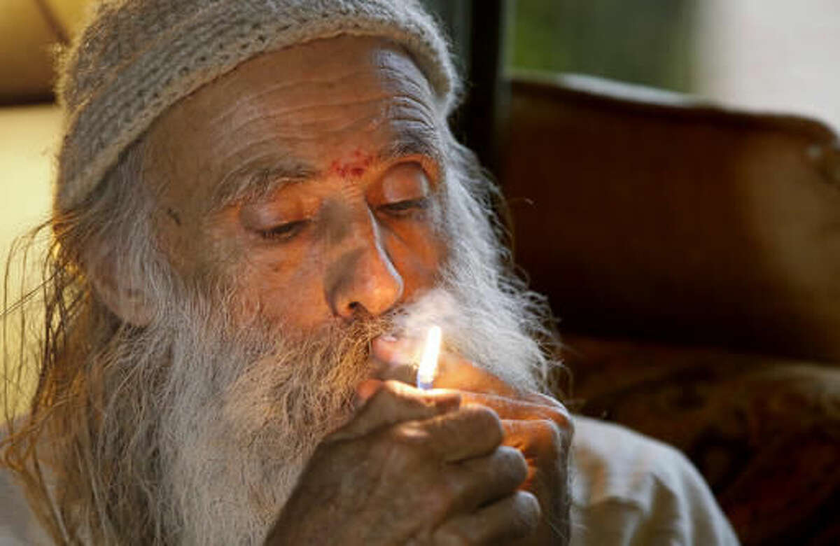 """In this Thursday, Oct. 13, 2016 photo, Swami Chaitanya lights a """"grower's joint"""" marijuana cigarette at his home near Laytonville, Calif. Chaitanya and his wife, Nikki Lastreto, who grow their """"Swami's Select"""" medical marijuana, support the passage of Proposition 64, the Nov. 8 ballot initiative, which would legalize the recreational use of marijuana. (AP Photo/Rich Pedroncelli)"""