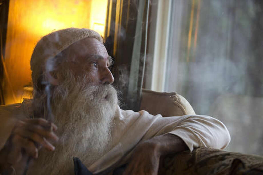 "In this Thursday, Oct. 13, 2016 photo, Swami Chaitanya looks out the window while smoking a ""grower's joint"" marijuana cigarette at his home near Laytonville, Calif. Chaitanya and his wife, Nikki Lastreto, who grow their ""Swami Select"" medical marijuana, support the passage of Proposition 64, the Nov. 8 ballot initiative, which would legalize the recreational use of marijuana. (AP Photo/Rich Pedroncelli)"