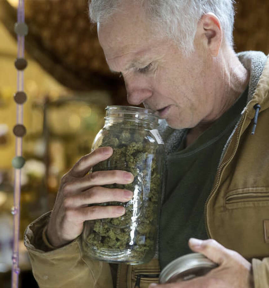 In this Thursday, Oct. 13, 2016 photo, Tim Blake checks the aroma of a jar of medical marijuana at his dispensary near Laytonville, Calif. Blake supports the passage of Proposition 64, the November ballot initiative which would legalize the recreational use of marijuana, saying it's the next big step for an industry emerging from the shadows. (AP Photo/Rich Pedroncelli)