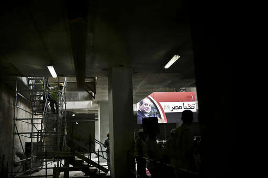 """A worker stands near a large poster of Egyptian President Abdel-Fattah el-Sissi with Arabic that reads, """"long live Egypt,"""" as the National Authority for Tunnels holds a press conference on the progress of the third line of the Cairo metro, in Egypt, Thursday, Oct. 27, 2016. Egypt hopes to attract much needed investment when it unleashes market forces with devaluation, subsidy cuts and reforms aimed at bringingan IMF bailout. But fears of a backlash from a public already straining under high inflation and unemployment are growing. (AP Photo/Nariman El-Mofty)"""