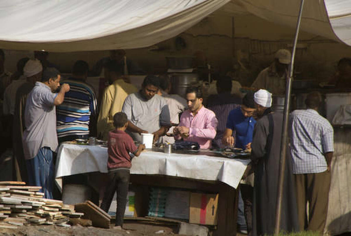 Egyptians eat fava beans, an inexpensive and filling local breakfast staple, at an open-air restaurant in Cairo, Egypt, Thursday, Oct. 27, 2016. Egypt hopes to attract much needed investment when it unleashes market forces with devaluation, subsidy cuts and reforms aimed at bringingan IMF bailout and greater investment. But fears of a backlash from a public already straining under high inflation and unemployment are growing. (AP Photo/Amr Nabil)