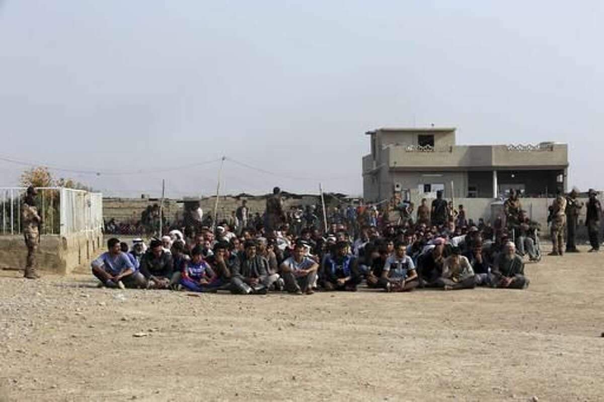 Iraq's elite counterterrorism forces gather villagers for preliminary investigation before taking them to displaced people camps in the village of Tob Zawa, about 9 kilometers (5.6 miles) from Mosul, Iraq, Tuesday, Oct. 25, 2016. The U.N. says it is closely monitoring the Mosul operation and the treatment of internally displaced civilians, or IDPs. (AP Photo/Khalid Mohammed)
