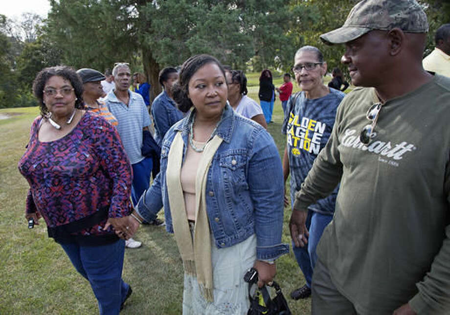 Stacey Payton, center, and Hollis Payton, right, the parents of a high school student, walk with supporters, in front of the Stone County Courthouse in Wiggins, Miss., Monday, Oct. 24, 2016. Johnson is demanding a federal investigation after the parents said four white students put a noose around their son's neck at school. (AP Photo/Max Becherer)