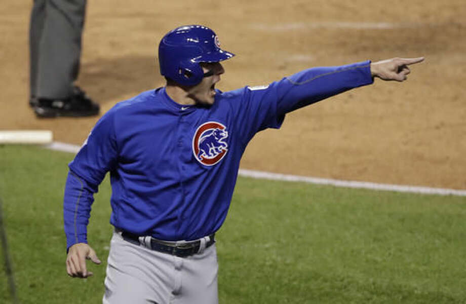 Chicago Cubs' Anthony Rizzo points to Kyle Schwarber after scoring on a hit during the third inning of Game 2 of the Major League Baseball World Series against the Cleveland Indians Wednesday, Oct. 26, 2016, in Cleveland. (AP Photo/Gene J. Puskar)