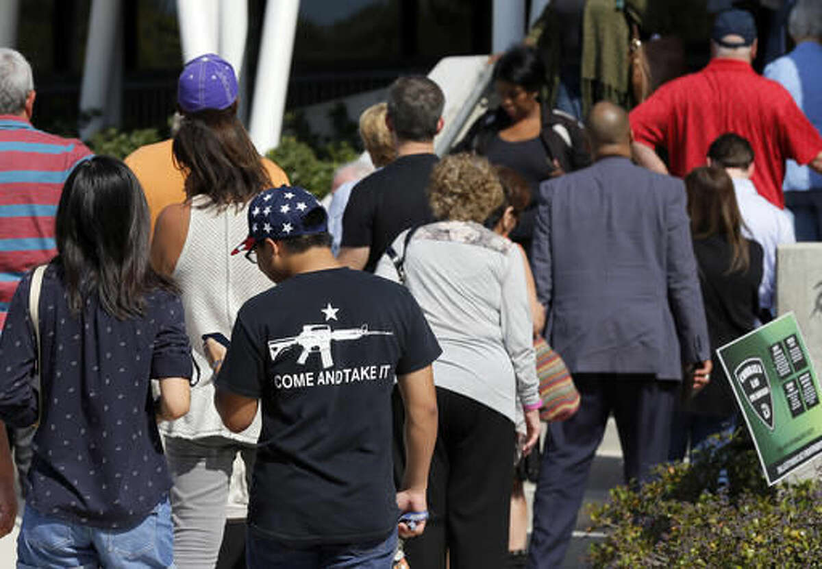 Jermaine Phua, left and Michael Nguyen, right, both University of Texas, Dallas students, stand in a long line waiting to cast their early votes, Thursday, Oct. 27, 2016, in Dallas. (AP Photo/Tony Gutierrez)