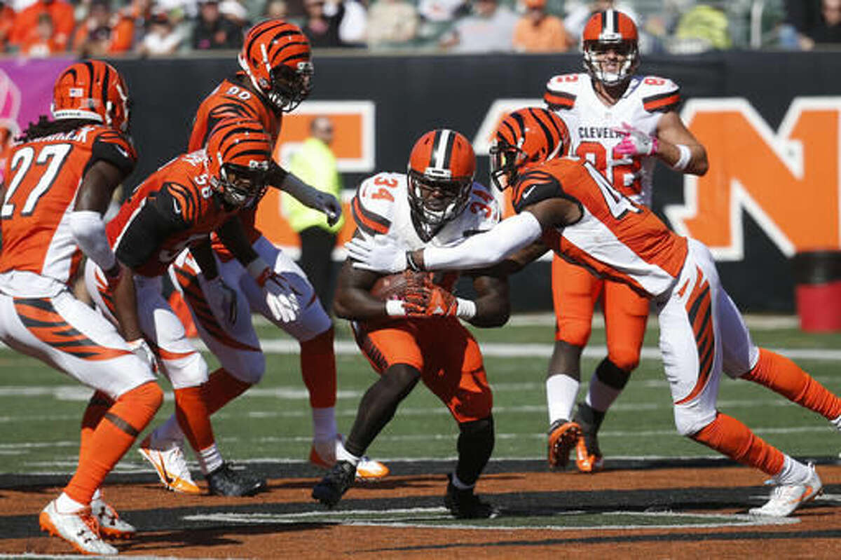 FILE - In this Sunday, Oct. 23, 2016, file photo, Cleveland Browns running back Isaiah Crowell (34) runs the ball through a host of Cincinnati Bengals defenders in the second half of an NFL football game in Cincinnati. The Bengals defense has had trouble against the rush all season long. They're hoping to get their problems fixed before they head to London to play Washington.(AP Photo/Frank Victores, File)