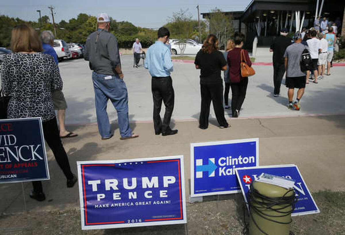 Early voters stand by campaign signage as they wait in line at a voting location, Thursday, Oct. 27, 2016, in Dallas. Republican presidential candidate Donald Trump is again raising the possibility of election rigging in a tweet that follows unsubstantiated claims in Texas of voters having their ballots changed.(AP Photo/Tony Gutierrez)