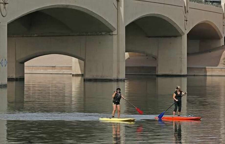 Two people take to the waters at Tempe Town Lake while paddle boarding as temperatures are expected to break records again Thursday, Oct. 27, 2016, in Tempe, Ariz. Arizona is in the midst of a heat wave that has made October one of the hottest on records. (AP Photo/Ross D. Franklin)