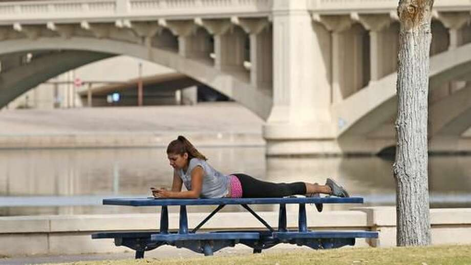 A woman relaxes next to Tempe Town Lake as temperatures are expected to break records again Thursday, Oct. 27, 2016, in Tempe, Ariz. Arizona is in the midst of a heat wave that has made October one of the hottest on records. (AP Photo/Ross D. Franklin)
