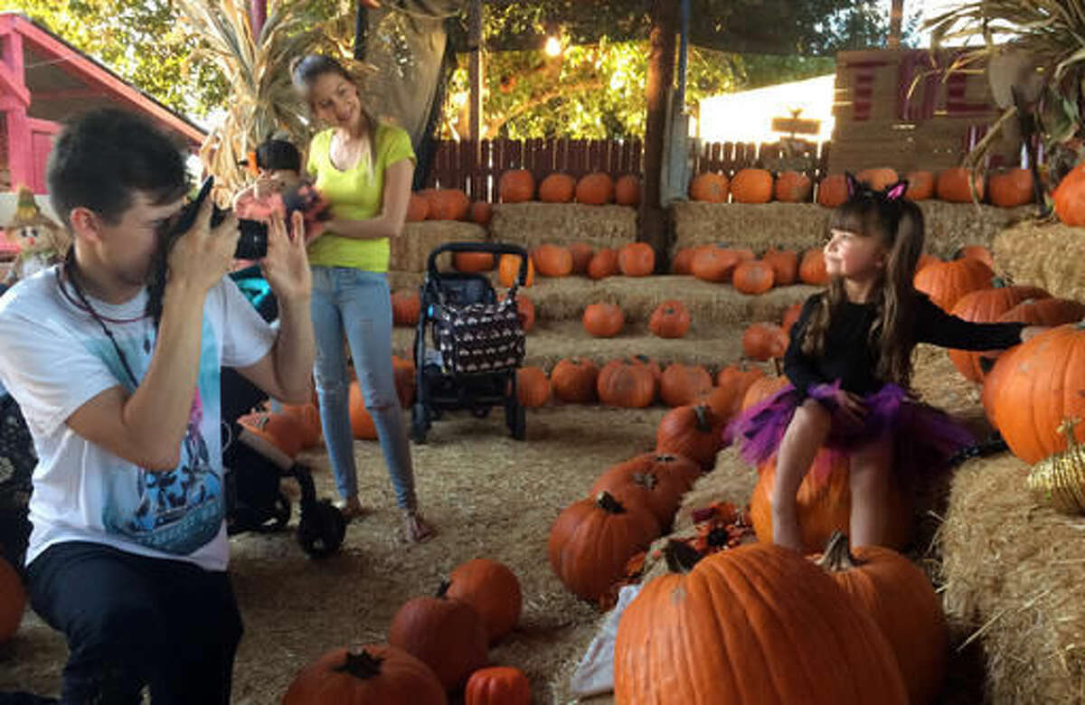 Gleen Pina takes a picture of his niece, 3-year-old Evany Pina, as his sister, Shirley Pina, looks on at a pumpkin patch in Glendale, Ariz., on Wednesday, Oct. 26, 2016. In Arizona, jack-o'-lanterns may not be the only things face-melting this Halloween. The state is in the midst of a heat wave that has made October one of the hottest in years, including lengthy runs of 90-plus degree days in Phoenix and Tucson that could break a record Thursday. (AP Photo/Terry Tang)