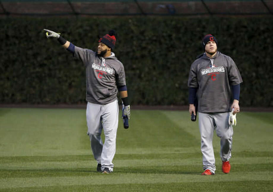 Cleveland Indians' Carlos Santana, left, and Roberto Perez walk out on the field for batting practice for Friday's Game 3 of the Major League Baseball World Series against the Chicago Cubs, Thursday, Oct. 27, 2016, in Chicago. (AP Photo/Charles Rex Arbogast)