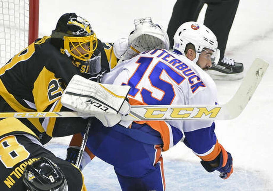 New York Islanders right wing Cal Clutterbuck (15) runs into Pittsburgh Penguins goalie Marc-Andre Fleury (29) during the first period of an NHL hockey game on Thursday, Oct. 27, 2016, in Pittsburgh. Clutterbuck was given a two-minute penalty for goaltender interference on the play. (AP Photo/Fred Vuich)