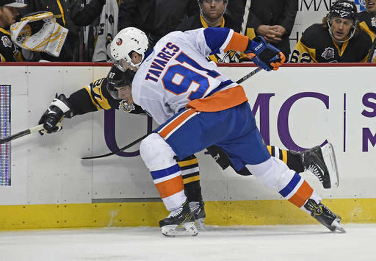 New York Islanders center John Tavares (91) checks Pittsburgh Penguins center Sidney Crosby (87) during the second period of an NHL hockey game on Thursday, Oct. 27, 2016, in Pittsburgh. (AP Photo/Fred Vuich)