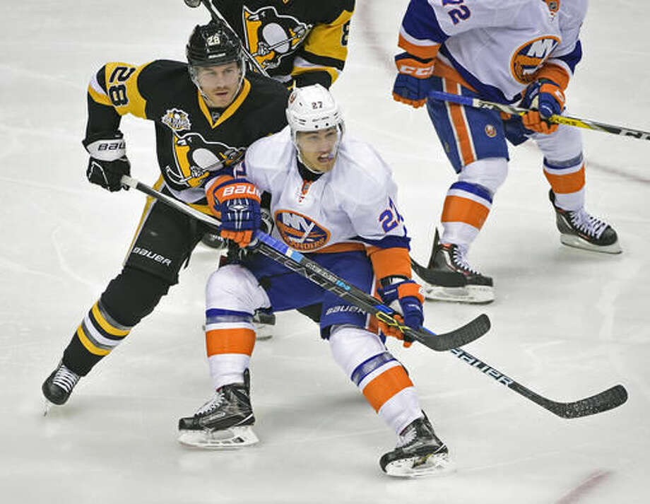 Pittsburgh Penguins defenseman Ian Cole (28) ties up New York Islanders left wing Anders Lee (27) in front of the net during the first period of an NHL hockey game on Thursday, Oct. 27, 2016, in Pittsburgh. (AP Photo/Fred Vuich)