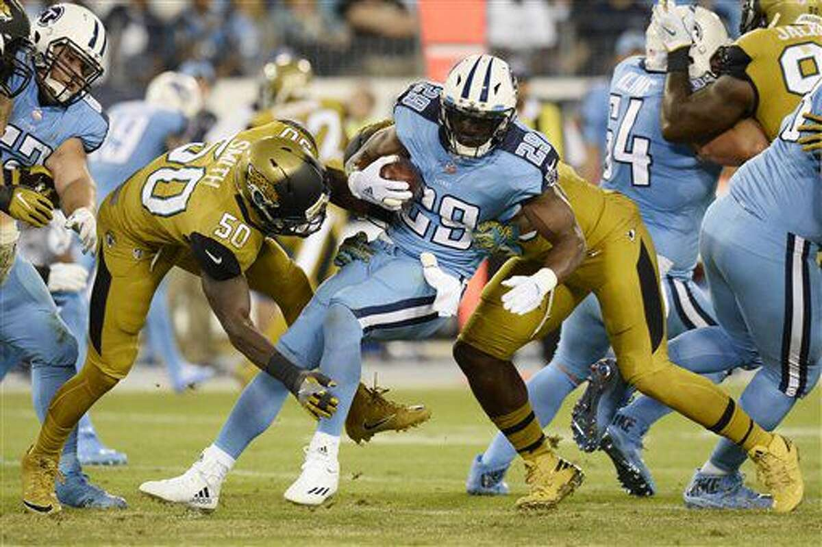 Tennessee Titans running back DeMarco Murray (29) is stopped by Jacksonville Jaguars linebacker Telvin Smith (50) and defensive end Dante Fowler, right, in the first half of an NFL football game Thursday, Oct. 27, 2016, in Nashville, Tenn. (AP Photo/Mark Zaleski)
