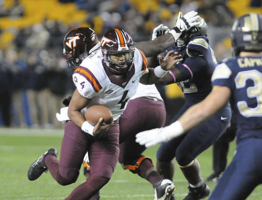 Virginia Tech quarterback Jerod Evans (4) picks up a first down against Pittsburgh in the first half of an NCAA college football game Thursday, Oct. 27, 2016, in Pittsburgh. (AP Photo/John Heller)