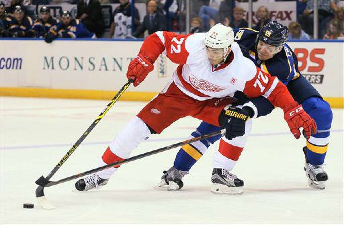 St. Louis Blues defenseman Colton Parayko, right, pokes the puck away from Detroit Red Wings center Andreas Athanasiou in the second period of an NHL hockey game Thursday, Oct. 27, 2016, in St. Louis. (Chris Lee/St. Louis Post-Dispatch via AP)