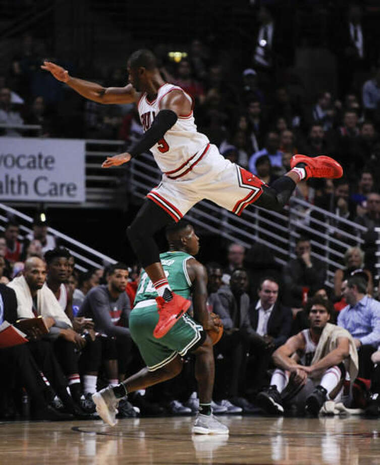 Chicago Bulls guard Dwyane Wade, top, leaps over Boston Celtics guard Terry Rozier (12) during the first quarter of an NBA basketball game Thursday, Oct. 27, 2016, in Chicago. (AP Photo/Matt Marton)