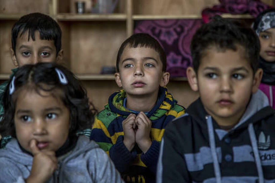 In this Thursday, Oct. 20, 2016 photo, Kashmiri children listen to their teacher as they attend an ad-hoc learning center at a local mosque in Srinagar, Indian controlled Kashmir. With daily life still paralyzed by strikes and rolling curfews, dozens of learning centers have popped up in people's homes or religious centers like mosques in Kashmir since August. The centers are doing more than just helping students prepare for upcoming exams, organizers said. They're keeping kids off the streets and giving them comfort amid a civilian uprising sparked when a popular rebel leader was killed in fighting Indian forces on July 8. (AP Photo/Dar Yasin)