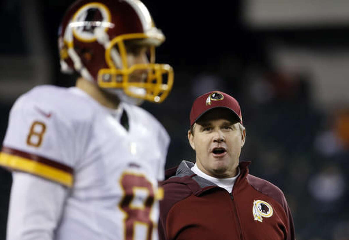 FILE - In this Dec. 26, 2015, file photo, Washington Redskins head coach Jay Gruden, right, watches quarterback Kirk Cousins warm up before an NFL football game against the Philadelphia Eagles in Philadelphia. Gruden is excited to face his former team in the Bengals. Gruden was Cincinnati's offensive coordinator from 2011-2013 and is trying in Washington to help Kirk Cousins grow like Andy Dalton did.(AP Photo/Matt Rourke, File)