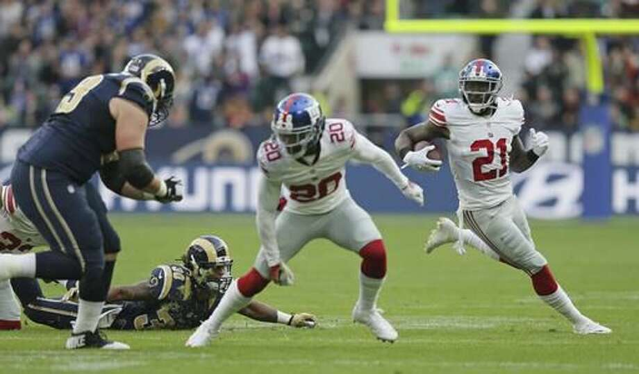 FILE - In this Oct. 23, 2016, file photo, New York Giants strong safety Landon Collins (21) runs enroute to scoring a touchdown during an NFL football game against Los Angeles Rams at Twickenham stadium in London. A multi-million dollar infusion in the offseason has transformed Steve Spagnuolo's unit from the worst in the NFL to one that is suddenly finding ways to win games. (AP Photo/Tim Ireland, File)
