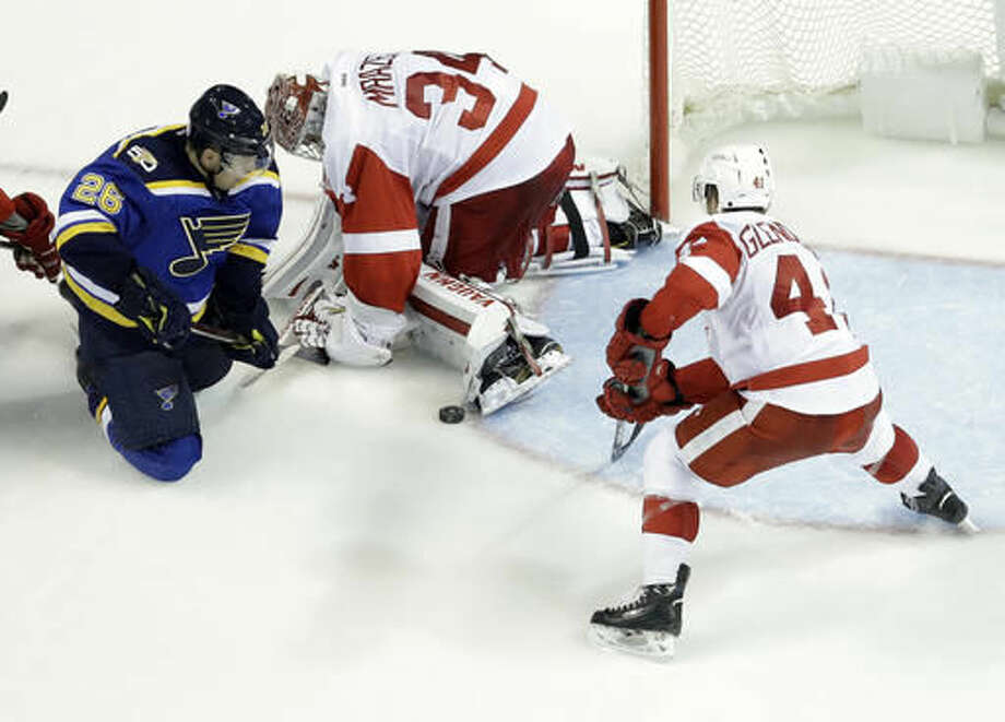 Detroit Red Wings goalie Petr Mrazek, of the Czech Republic, stops a puck with his foot as teammate Luke Glendening, right, and St. Louis Blues' Paul Stastny, right, watch during the third period of an NHL hockey game Thursday, Oct. 27, 2016, in St. Louis. (AP Photo/Jeff Roberson)