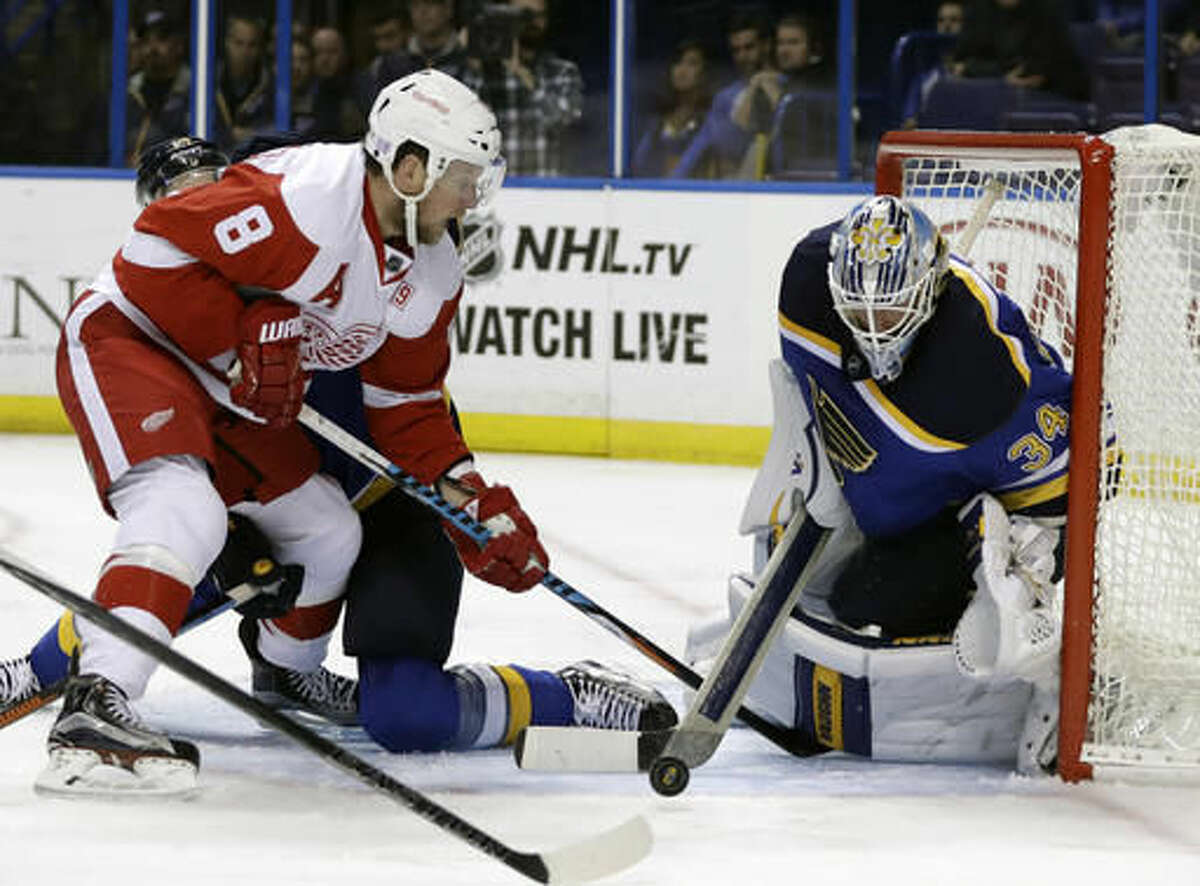 Detroit Red Wings' Justin Abdelkader, left, is unable to reach the puck as St. Louis Blues goalie Jake Allen defends during the third period of an NHL hockey game Thursday, Oct. 27, 2016, in St. Louis. (AP Photo/Jeff Roberson)
