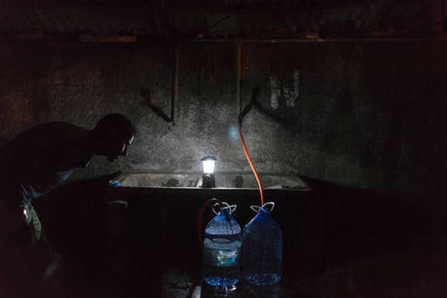 """In this Oct. 10, 2016 photo, Samuel Alves de Andrade watches as he fills a container with water from the Sao Braz water pipe in, Colatina, Brazil. """"Since the environmental disaster we starting collect this water. We don't know how this water is, but I believe it is better than the water from the (Doce) river."""" Nov. 5 will mark the one-year anniversary when a dam of mine waste broke open, polluting hundreds of miles of rivers, streams and forest land in the Doce River Valley. (AP Photo/Leo Correa)"""