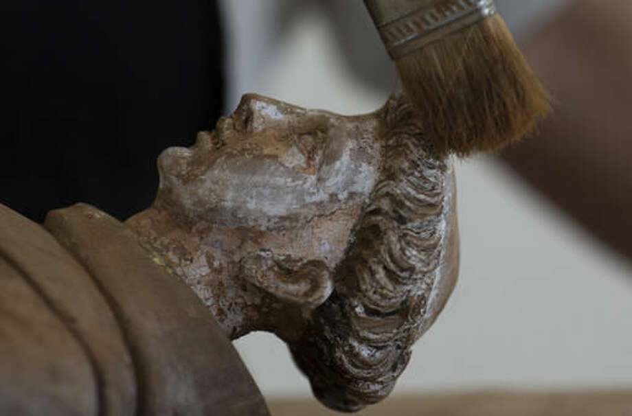 In this Oct. 14, 2016 photo, restorer Suely Gomes brushes away mud caked on a 19th century statue of Saint Anthony, at a recovery center in Mariana, Brazil. Almost two thousand religious icons from surrounding villages in the Doce River Valley, were washed into the river because of a mudslide triggered by the Nov. 5, 2015 failing of a dam holding back a giant pond of mine waste. (AP Photo/Leo Correa)