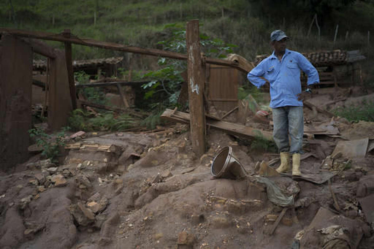 In this Oct, 13, 2016 photo, Geraldo de Oliveira stands on the rubble of his home destroyed by a Nov. 5, 2015 mudslide unleashed by the bursting of a mine-waste basin, in Paracatu, Brazil.