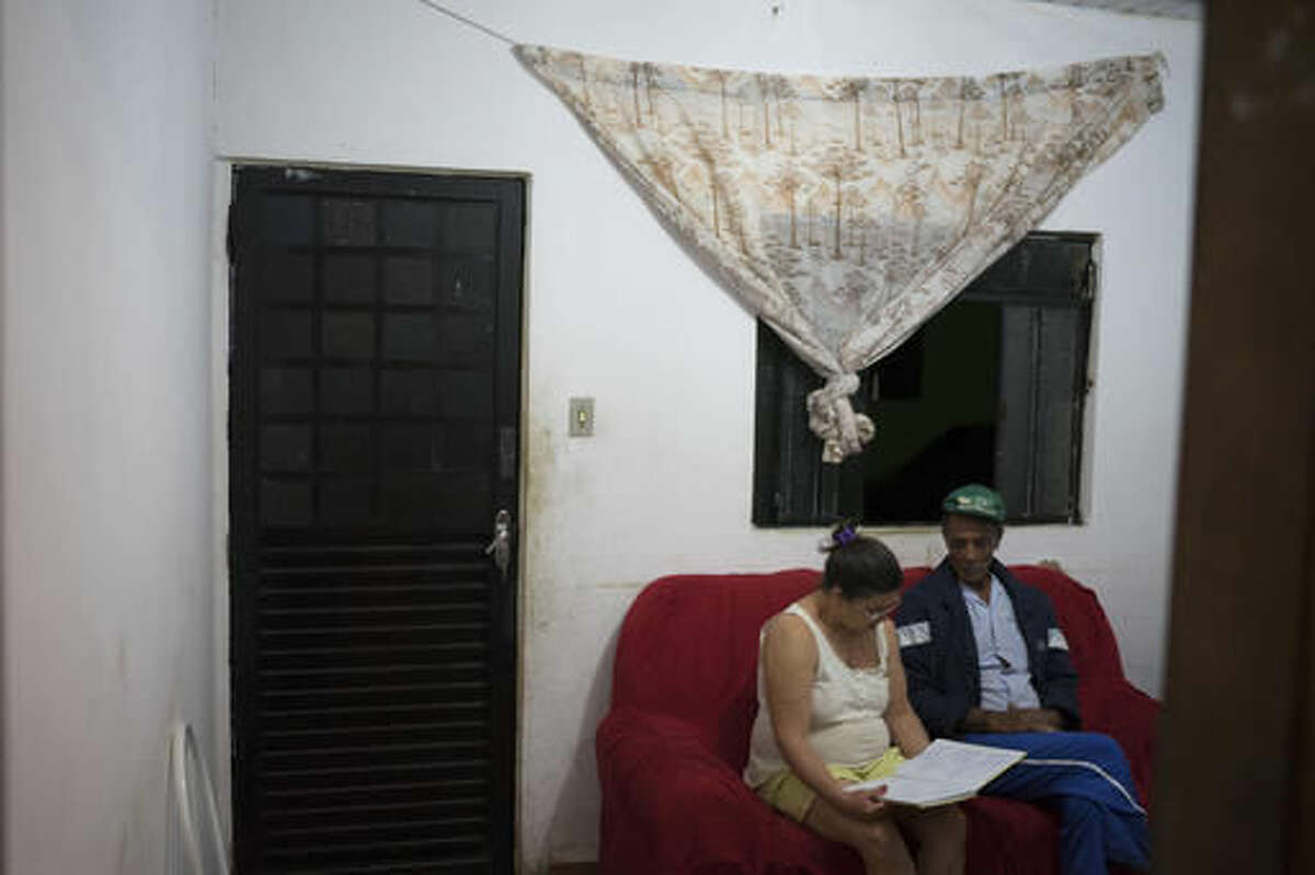 In this Oct. 13, 2016 photo, Maria do Carmo Pereira Ramos, left, sits next to her husband Jose do Patrocinio de Oliveira, in Mariana, Brazil, as she reads aloud a poem she wrote about the tragedy of their hometown. She wrote,